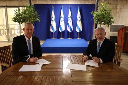 Netanyahu, à direita, assina com o centrista Beny Gantz o acordo alcançado nesta segunda-feira.