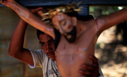 Homem carrega estátua de Jesus Cristo antes de procissão em El Salvador.