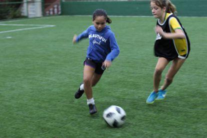 Lara, à esquerda, disputa a bola com outra menina.