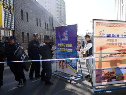 Policiais chineses tampam com cartazes o acesso ao tribunal onde é julgado um professor em Urumqi (Xinjang) em setembro.