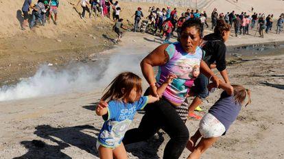 Família foge das bombas de gás lacrimogêneo próximo à fronteira entre os EUA e o México neste domingo, 25