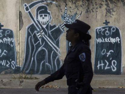 Uma oficial de policial caminha em um bairro controlado pela mara