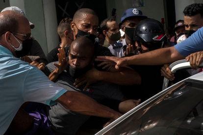 Vários policiais detêm um manifestante durante os protestos contra o Governo cubano na Havana, neste domingo.