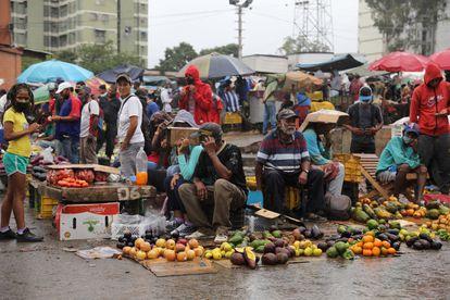 Vendedores trabalham no mercado de rua Coche, em Caracas, debaixo de chuva.