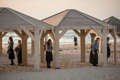 Jovens religiosas rezam sob quiosques em uma praia de Tel Aviv.