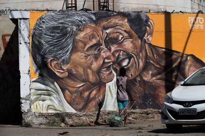 Uma mulher com carrinho de compras fala e gesticula em frente à pintura, como se estivesse conversando com o casal retratado.