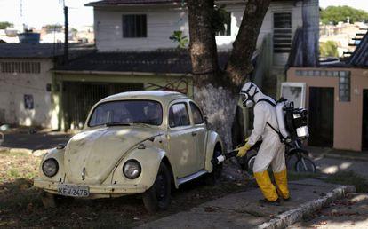 Um trabalhador fumiga um carro, ontem no Brasil.