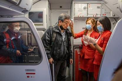 Duas aeromoças medem a temperatura de passageiros num embarque no aeroporto de Incheon (Coreia do Sul).