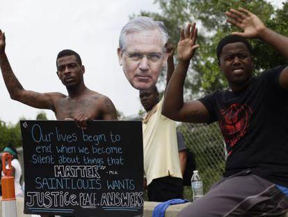 Manifestantes mostram um cartaz com o rosto do governador do Missouri, Jay Nixon.