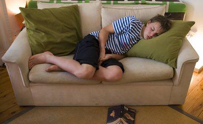 Adolescente dorme no sofá durante leitura de livro. GETTY