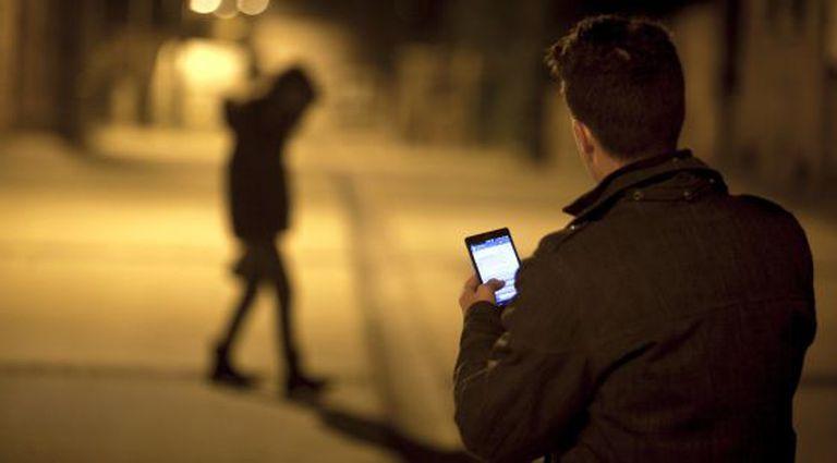 Um homem usa seu celular diante da silhueta de uma jovem.