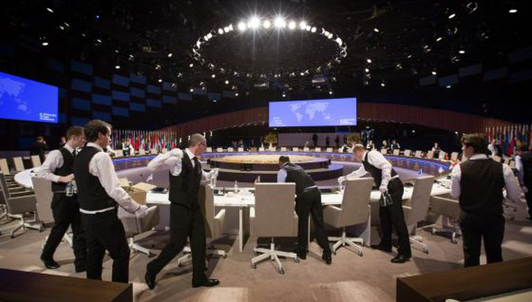 Garçons preparam as mesas na Cúpula Nuclear da Holanda, nesta terça-feira.