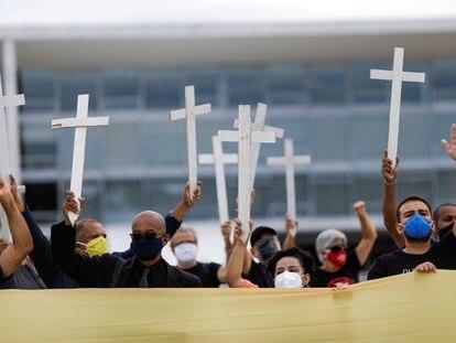 Manifestantes carregam cruzes em protesto contra o presidente Jair Bolsonaro, nesta sexta.