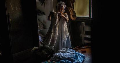 Mãe Merinha olha as roupas de santo queimadas.