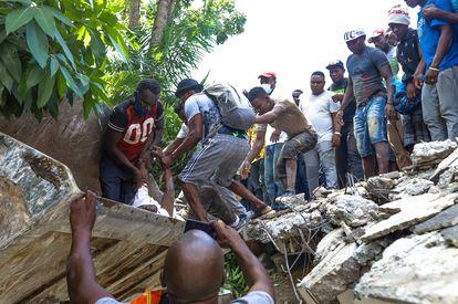 Haitianos se mobilizam para tentar encontrar sobreviventes sob os escombros, em Los Cayos, Haití.
