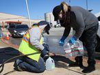 KYLE, TEXAS - FEBRUARY 20: Lucas Velarde and Erin Purdy (L-R) fill water jugs for people at a drive through water distribution center setup at Jack C Hays High School on February 20, 2021 in Kyle, Texas. Winter storm Uri brought historic cold weather causing people to lose their city water source as pipes broke throughout the area.   Joe Raedle/Getty Images/AFP == FOR NEWSPAPERS, INTERNET, TELCOS & TELEVISION USE ONLY ==