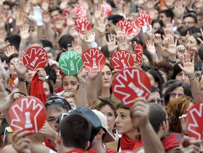 Milhares de pessoas erguem as mãos durante a concentração na praça central de Pamplona contra a agressão à jovem.