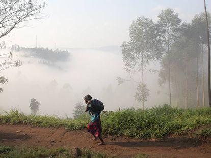 Uma criança vai para a escola levando sua mochila no Congo.