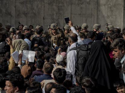 Um homem segura seu passaporte diante dos militares que guardam o aeroporto de Cabul.
