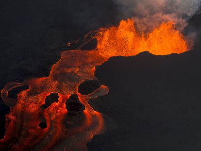 FILE - In this June 10, 2018 photo, lava from the Kilauea volcano continues to erupt from a fissure and forms a river of lava flowing down to Kapoho in Pahoa, Hawaii. (AP Photo/L.E. Baskow, File)
