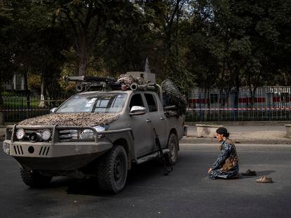 Um combatente talibã reza diante de um veículo militar, na sexta-feira em Cabul.