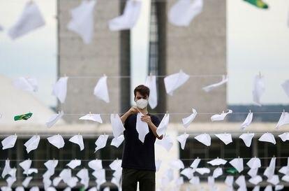 Membro da ONG Rio de Paz instala lenços em memorial para vítimas da covid-19 em frente ao Congresso Nacional, nesta segunda.