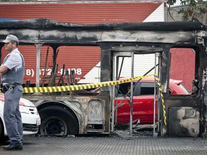 Um policial em frente a um ônibus queimado na zona sul de São Paulo.