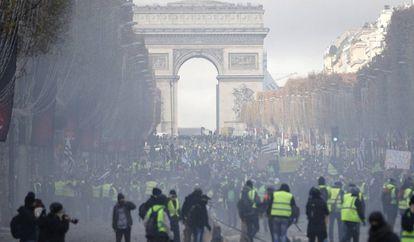 Uma nuvem de gás envolve os manifestantes, que levantaram barricadas na avenida Champs Élysées.