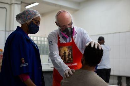 Padre Júlio Lancellotti acolhe um morador de rua de São Paulo junto com uma agente social da Prefeitura.