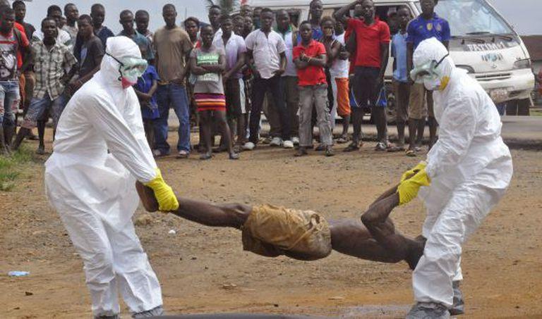Trabalhadores da saúde retiram cadáver de homem suspeito de morrer de ebola.