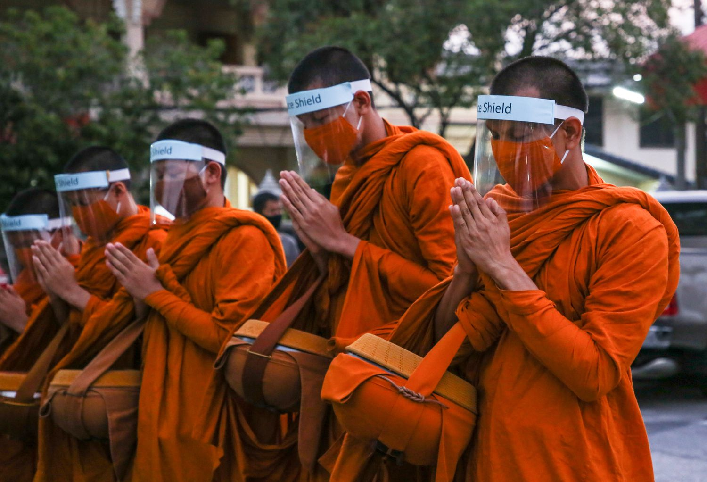 Monges usam máscaras de proteção contra a coronavírus, enquanto pedem doações em Bangkok, na Tailândia, nesta quarta-feira.