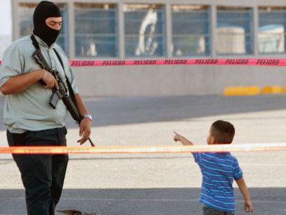 Um menino e um policial na cena de um crime.
