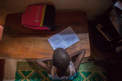 Leticia Amongin, de oito anos, faz a lição de casa com a pouca luz que entra pela janela de sua casa em Uganda.