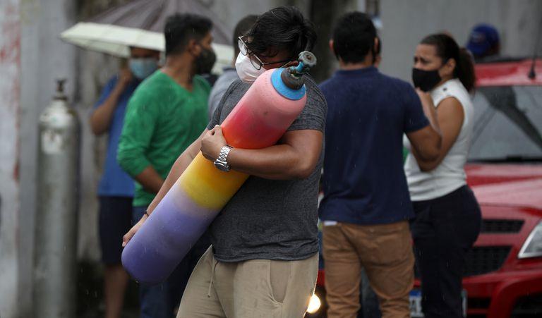 Um homem carrega um cilindro de oxigênio em Manaus.