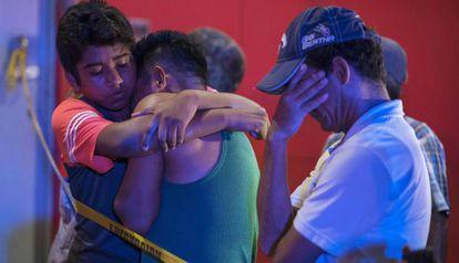 Várias pessoas se abraçam após um tiroteio que causou 23 mortos em um bar em Veracruz (México) em agosto.