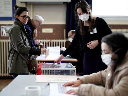 Eleitores com máscaras em uma seção eleitoral de Paris, neste domingo.