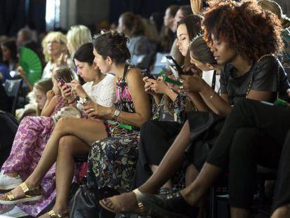 Mulheres olham o celular durante a semana da moda de Tel Aviv (Israel)