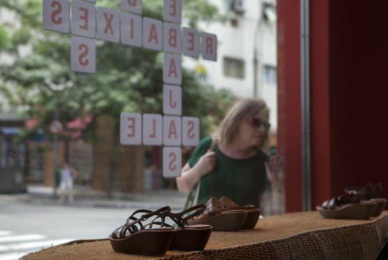 Mulher olha para vitrine em promoção em São Paulo.