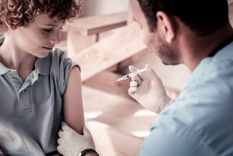 Um médico vacina a uma criança.