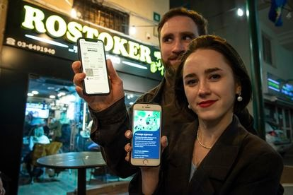 Olga Rerbo, de 29 anos, e Nathan Read, de 32, mostram o passe verde em seus celulares antes de entrarem em um bar em Ramat Gan, na região metropolitana de Tel Aviv.
