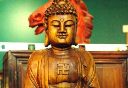 Buda com a suástica em sentido anti-horário (braços voltados para a esquerda) gravada no peito. Na cultura e religião budistas, a suástica é um símbolo de paz e prosperidade. Pode girar em um ou outro sentido, mas desde meados do século XX é feita quase sempre à esquerda, para diferenciar-se da cruz do Reich.
