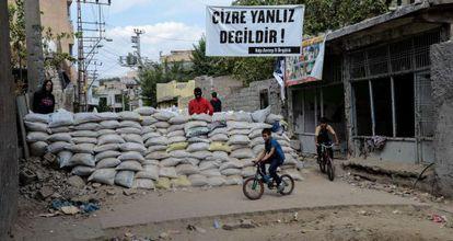 Crianças passam por uma das barricadas erguidas na localidade de Cizre por jovens curdos simpatizantes do PKK.