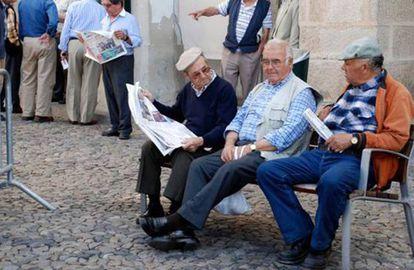 Aposentados portugueses leem jornais em uma rua.