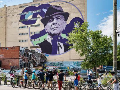 Ciclistas diante de um mural de Leonard Cohen em um edifício de Montreal, cidade natal do cantor canadense.