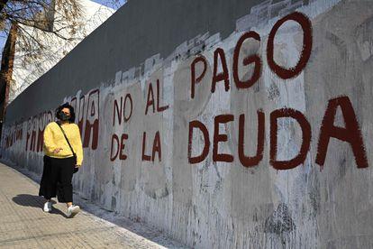 Uma mulher passa em frente a uma pichação contra o pagamento da dívida, em Buenos Aires.