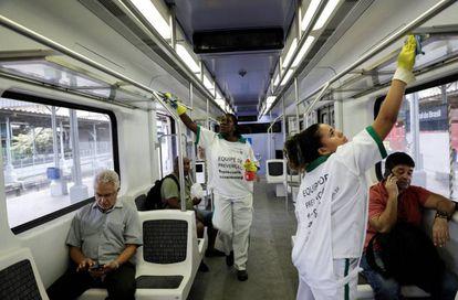 Duas mulheres desinfectam o vagão de um trem no Rio de Janeiro para combater o coronavírus.