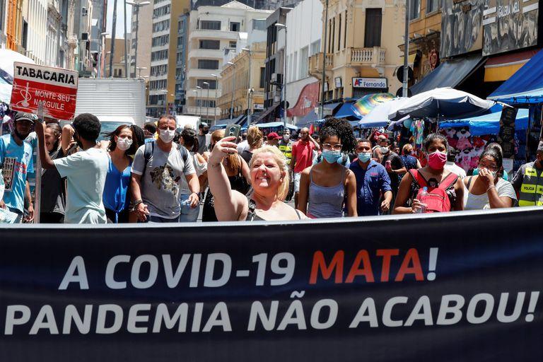 """Uma mulher sem máscara, no centro de São Paulo, tira uma selfie atrás de uma faixa que diz: """"A Covid-19 mata. A Pandemia não acabou""""."""
