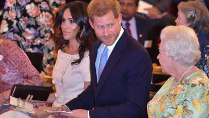 Elizabeth II, o príncipe Harry e Meghan Markle, em uma cerimônia de entrega de prêmios no palácio de Buckingham, em junho de 2018.