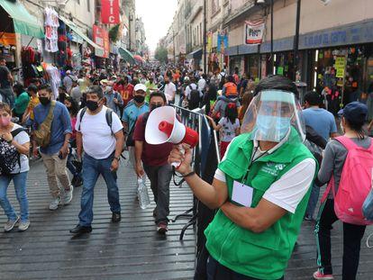 Um funcionário promove o distanciamento social em uma movimentada rua comercial do centro histórico da Cidade do México.