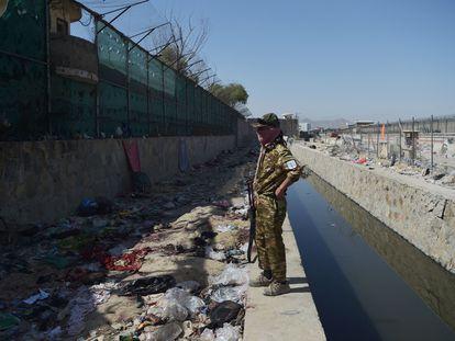 Um talibã em meio a restos de roupas ensanguentadas depois do atentado na entrada do aeroporto de Cabul na quinta-feira.